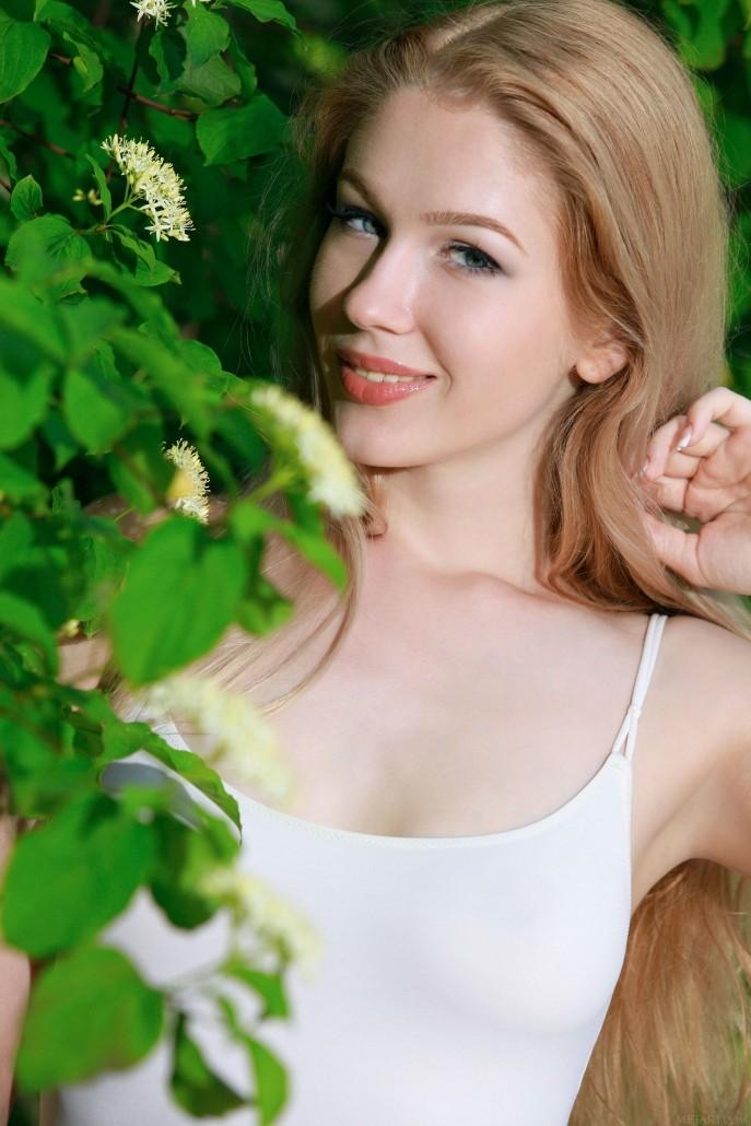 Голая Сабрина позирует в зелёном саду.