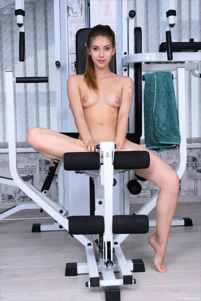 На фото голая спортивная девушка в тренажёрке.