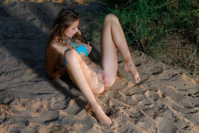Девушка рассматривает пизду на берегу реки.