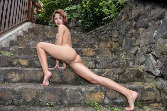 Пиздатая тёлка раздевается на ступеньках старого дома.