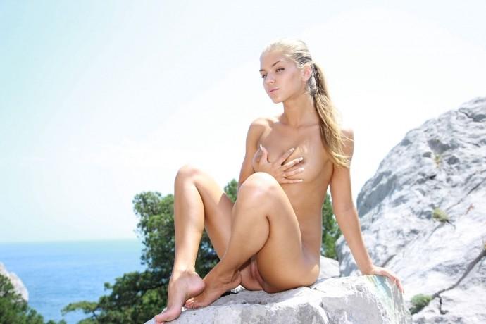 Девушка загорает голая на прибрежной скале.