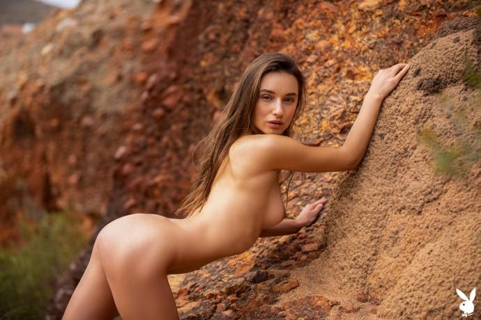 Голая Gloria Sol изучает скалистую местность.