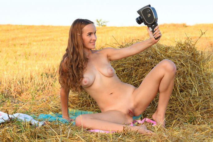 Голая девушка в поле с ретро видеокамерой.