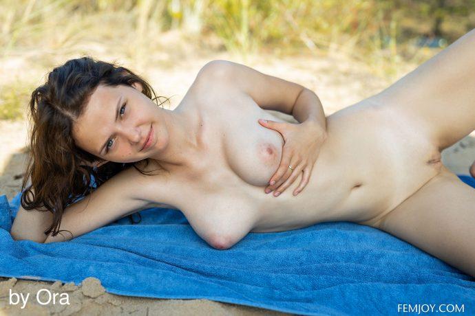 Голая студентка загорает на пляже.