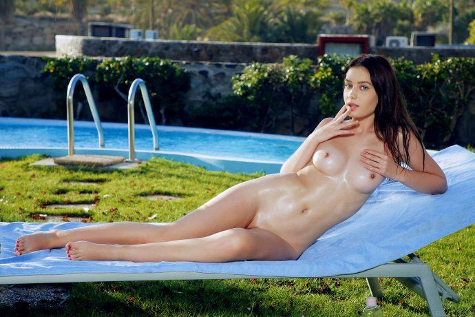 Девушка ласкает норку возле бассейна.