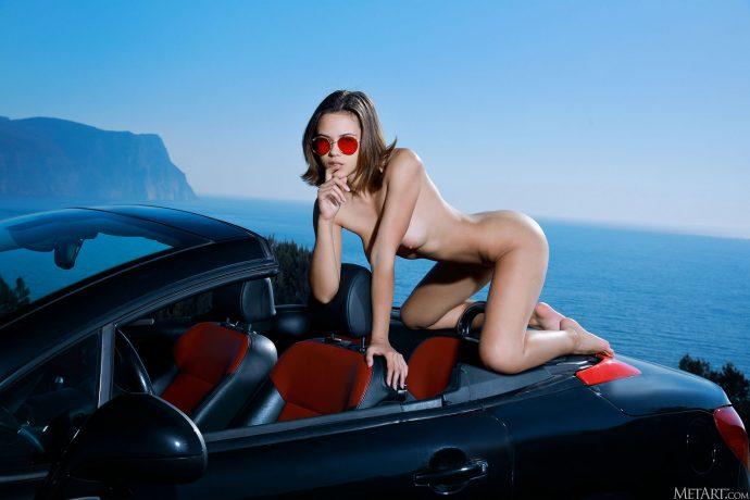 Голая девушка в кабриолете на фоне моря