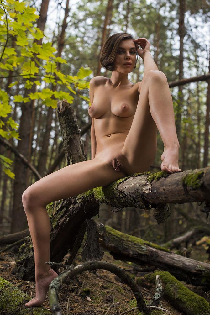 Голая девушка в лесу играет в фотомодель